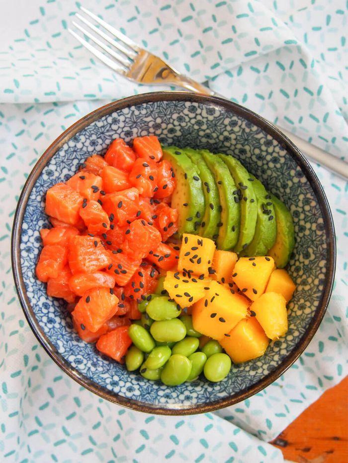 mangue fèves tranches d avocat saumon coupé en cubes dans un bol saupoudré de graines de sésame noir