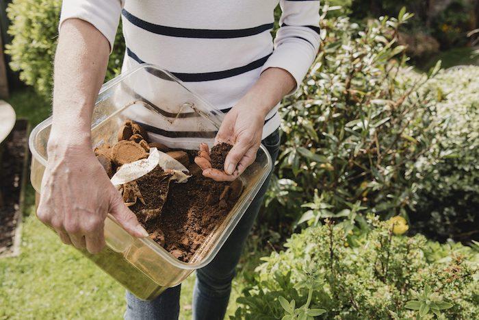 marc de café potager une femme qui tient un contenaire de marc de café dans le jardin