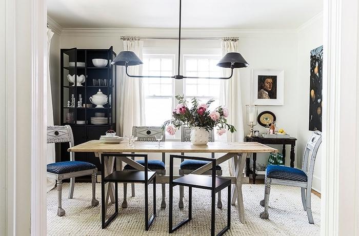 meuble salle à manger tapis blanc table bois chaises noires lustre meuble rangement ouvert noir portraits