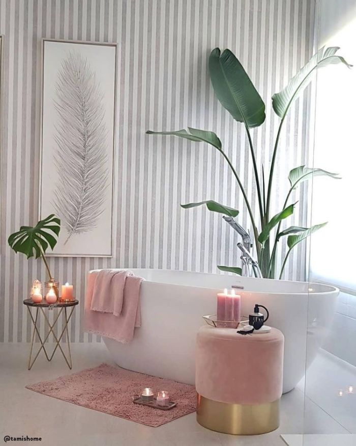 modele salle de bain avec baignoire blanche accents rose poudré tabouret tapis plaid rose plantes vertes bougies parfumées