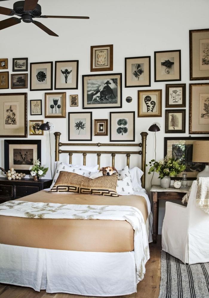 mur de cadres noirs et marron tete de lit fait maison peinture métallisée laiton meubles bois foncé ventilateur plafond
