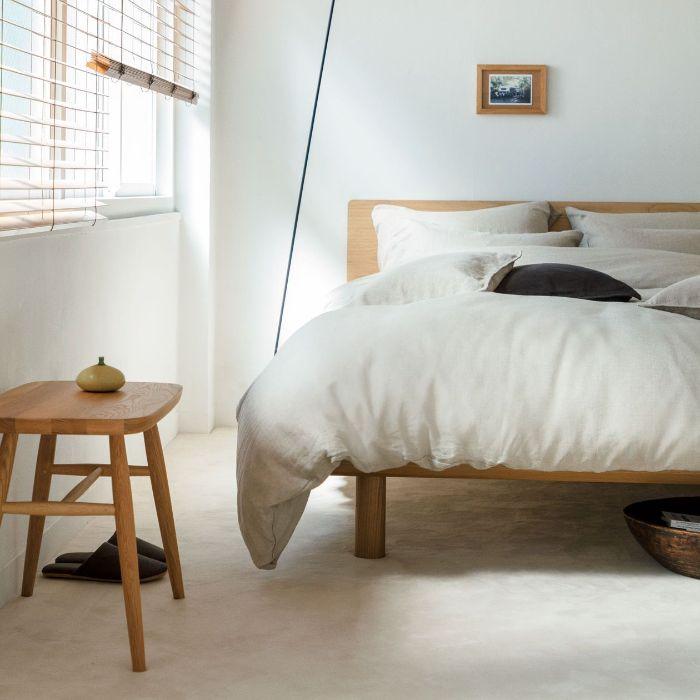 murs et sol blancs linge de lit blan sur lit de bois et table de nuit bois exemple chambre japonaise style minimaliste
