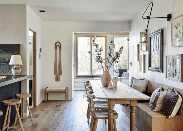murs lambris blancs cadres originaux canapé gris parquet bois clair ilot central entouré de tabourets bois vase rempli de coton