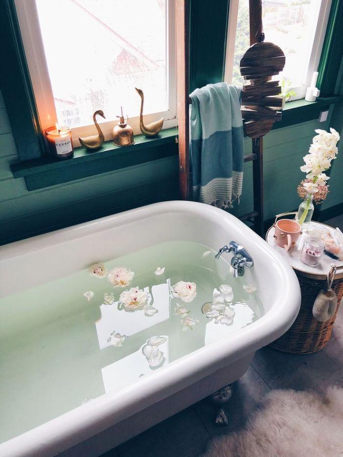 murs repeints de bleu baignoire blanche bout de baignoire tressé avec plateau marbre petites décorations échelle salle de bain