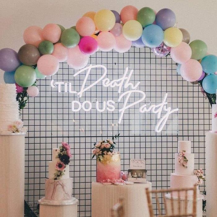 néon led sur un mur en carrelage sous un arc de ballons derrière des gateaux de marriage