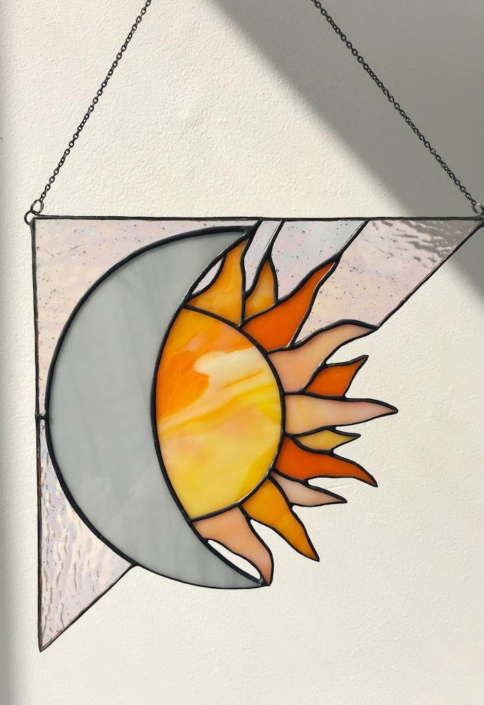 peinture sur verre avec une fogure de solei suspendu a un collier