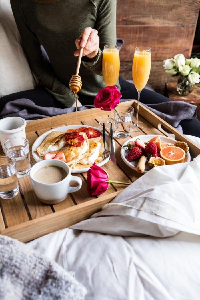 petit déjeuner au lit plateau bois tasse de café verre eau rose jus de fruits assiettes fruits