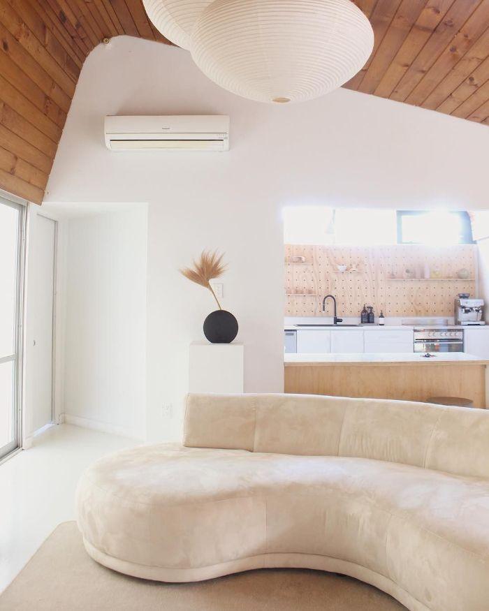 plafond revetu de bois murs blancs canapé blanc cassé deco panneau performé en crédence meuble cuisine bas bois