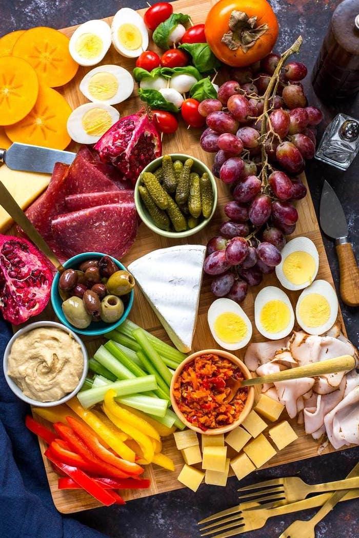 planche apéritive avec des oeufs des fruits et des legumes et des raisins et des fourchettes