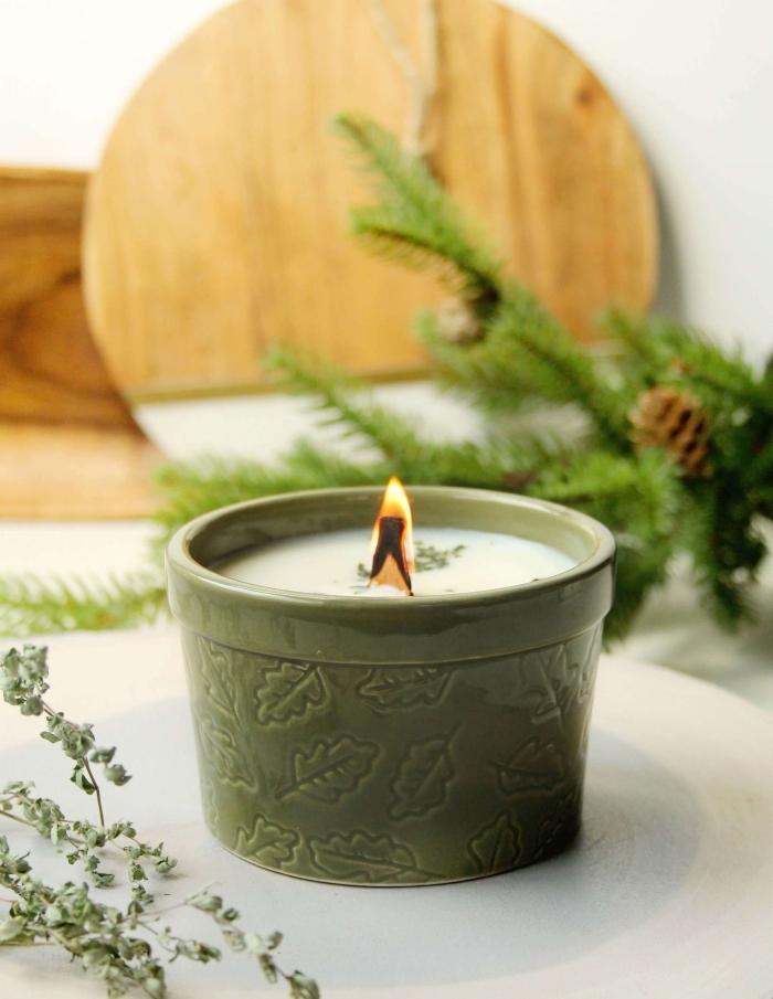 planche bois bougie décorative contenant pot vert motifs feuilles branches de sapin pommes de pin