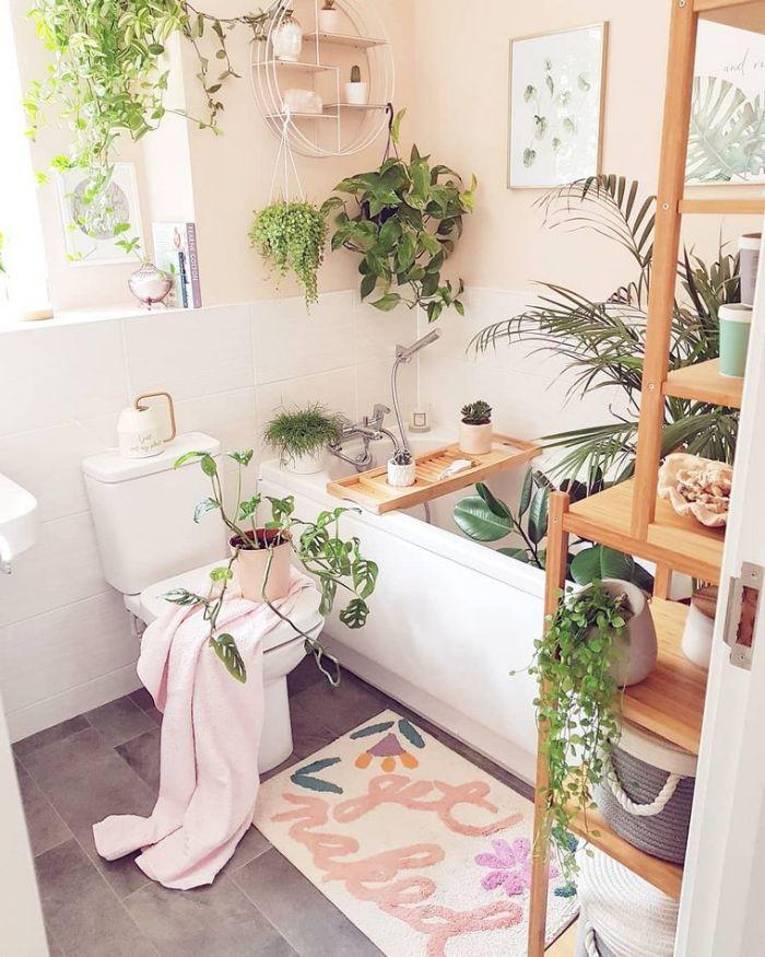 plantes vertes salle de bain gris et blanc avec baignoire blanche posée murs rose pale etagere salle d ebain bois