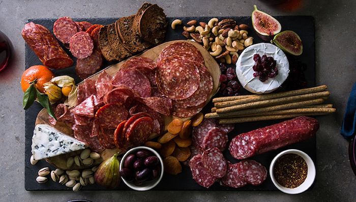 plateau apérifits en style européen avec des salamis des dex nois et des fromages sur une plaque noire