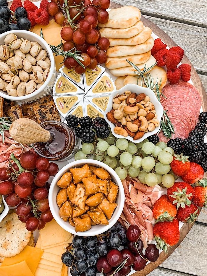 plateau apero avec des charcuteries des fromages des fruits et des noix sur un plateau ronde en bois