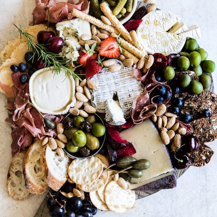 plateau charcuterie avec des crquelins et des olives differentes types de fromage avec des olives