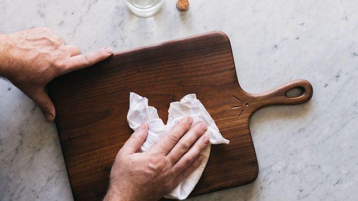plateau charcuterie deux mains qui essuyent une planche en bois sur un comptoir en marbre