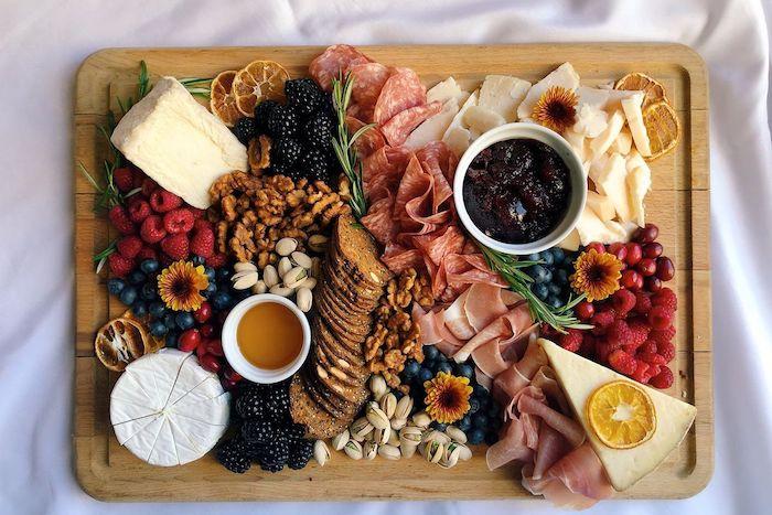 plateau charcuterie fromage moderne avec des fruits des noix et de la confiture garnis avec fleurs comestible