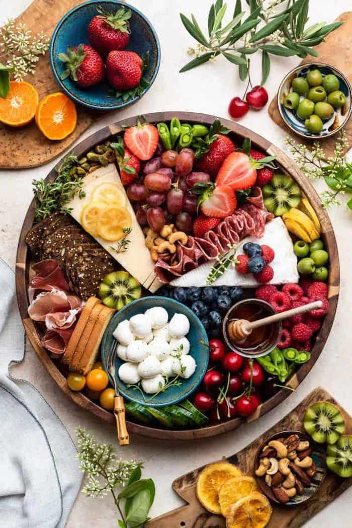 plateau de charuterie avec une abondance des fruits et des legumes et des noix sur une table avec une nappe dans deux bols