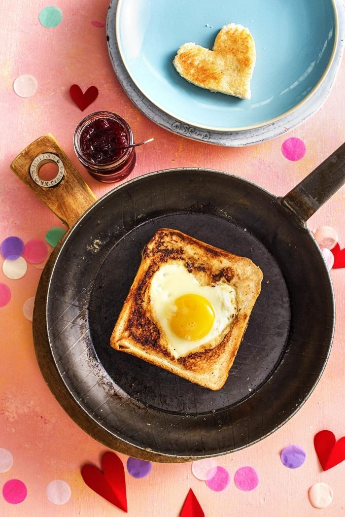 poêle petit déjeuner amoureux assiette ronde bleue pain doré oeuf confitures coeurs en papier