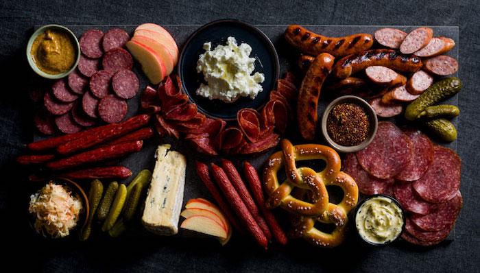 présentation plateau charcuterie avec differentes types de viandes des corniches et des bretzel sur une table noir