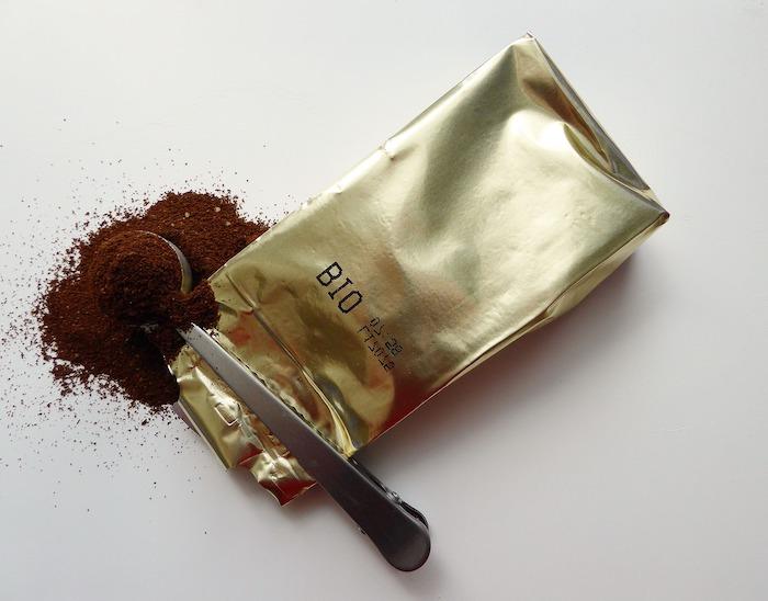 que faire avec le marc de café un paquet de cafe dorée et une couillère sur une surface blanche