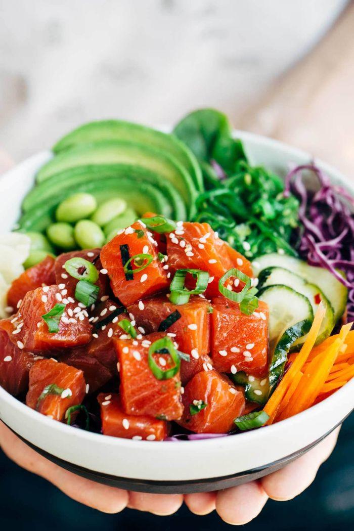 recette bowl saumon avec multitude de legumes frais carottes concombre chou rouge tranches d avocat et feuilles verdures