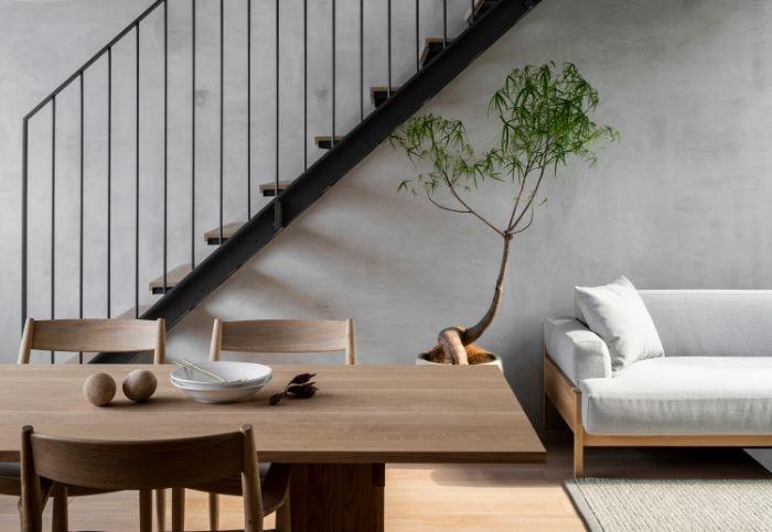 salle à manger chaise et table bois ouverte sur salon minimaliste en canapé de bois avec coussin blanc mur gris plante verte parquet bois clair