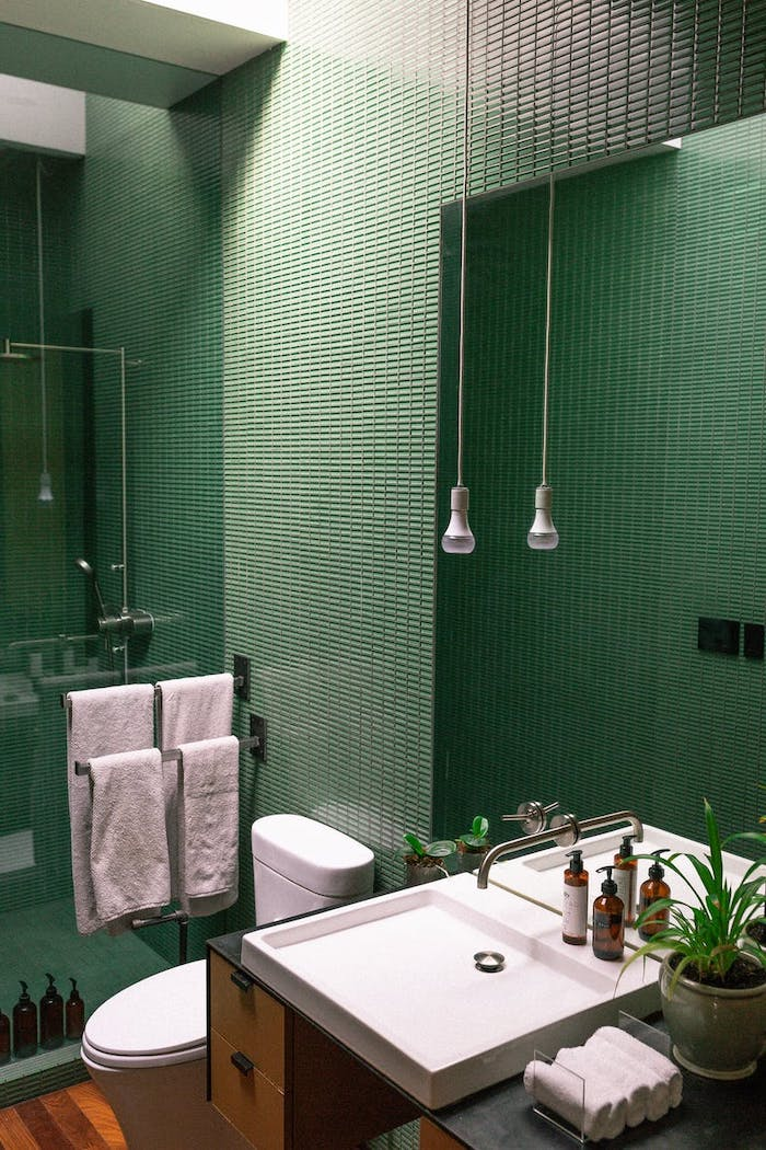 salle de bain avec un carrelage mosaique vert et deux lampes suspendus