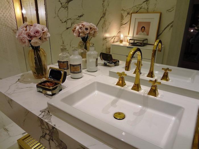 salle de bain avec un lavabo doree et une vase a fleurs a coté