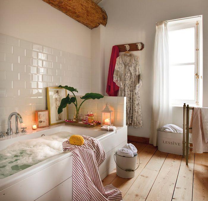 salle de bain blanche avec sol bois plancher vintage rideaux transparents poutre apparente bois lanterne bougie