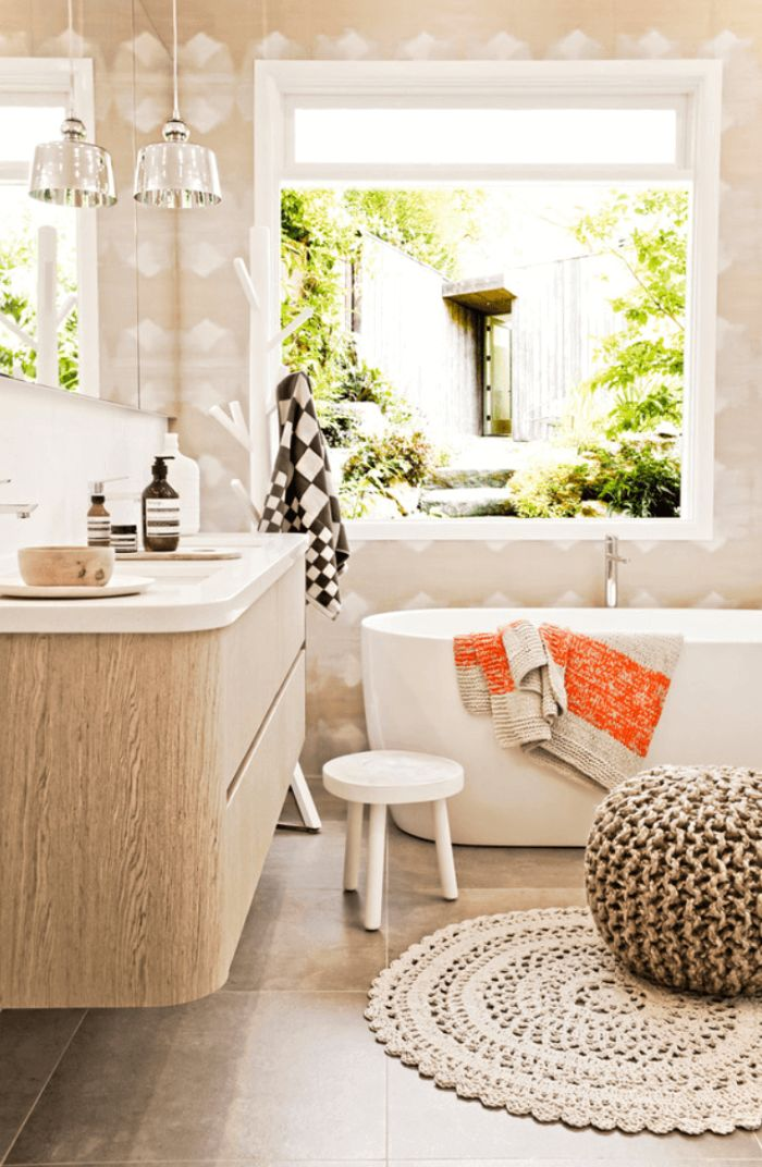 salle de bain bois avec carrelage sol gris baignoire blanche mur blanc et beige pouf gris tapis tressé