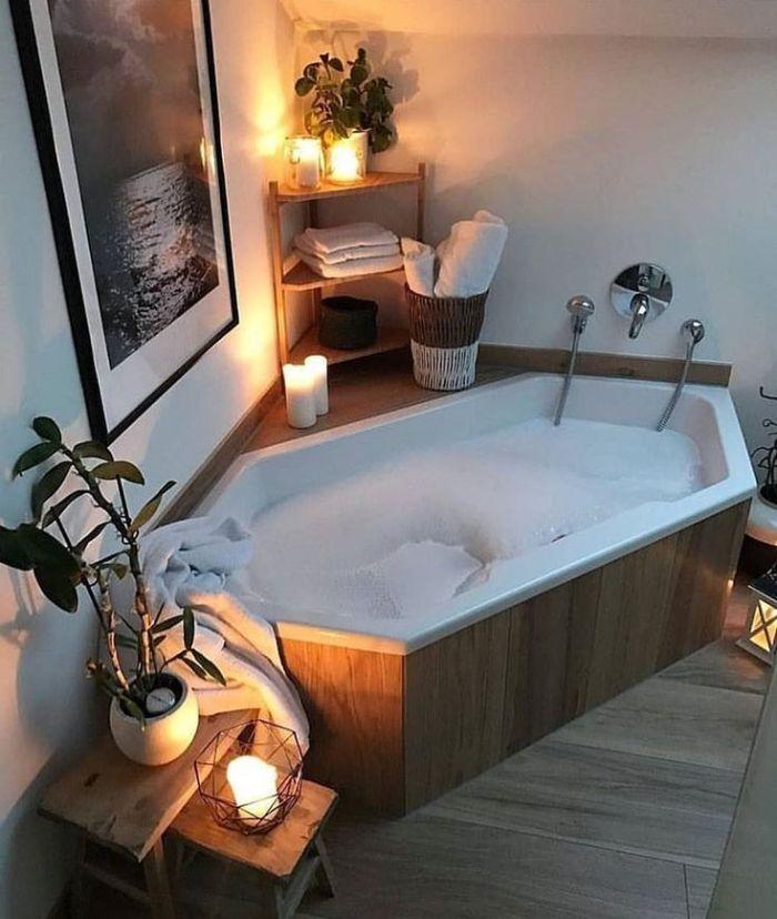 salle de bain bois et blanc avec lumière tamisée bougies plantes vertes et habillage baignoire bois