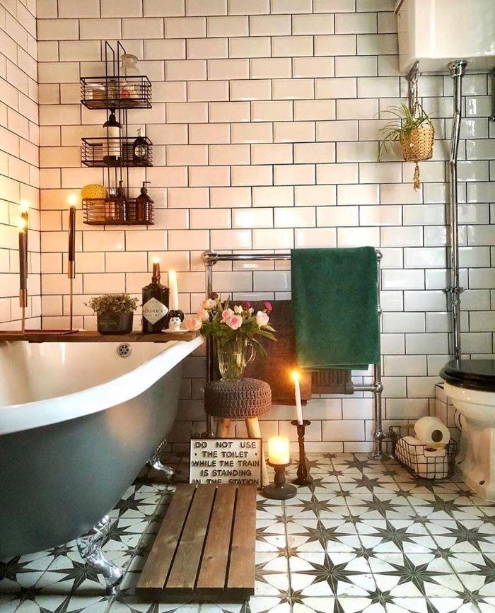 salle de bain cocooning avec carrelage metro blanc baignoire ancienne grise bougies décoratives étagères industrielles