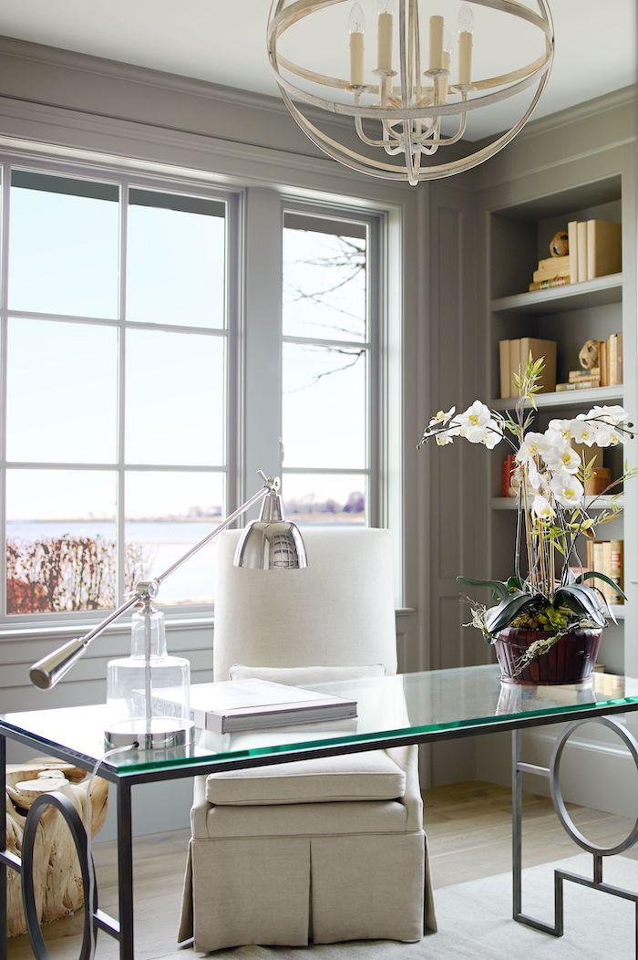 salon moderne 2021 un bureau en verre et fauteuil en tissu blanc décorée une orchidée
