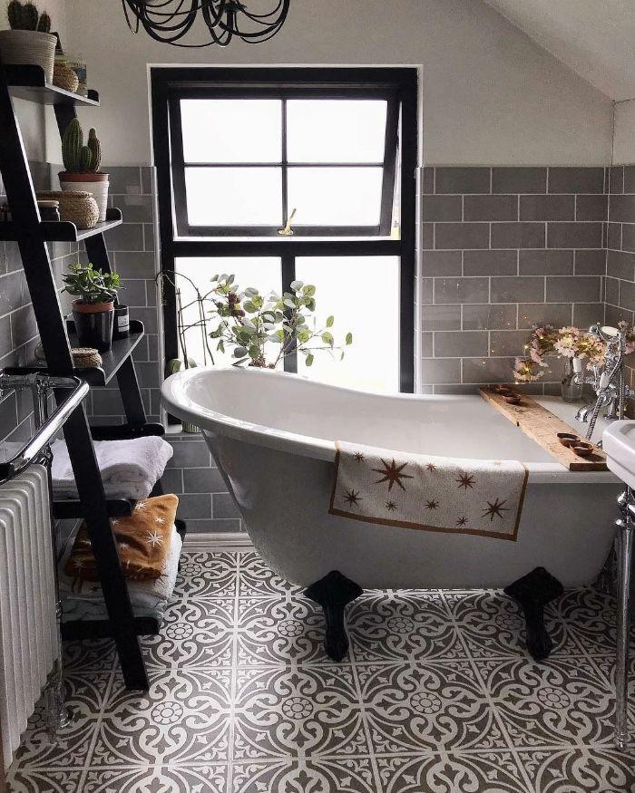 sol carreaux de ciment murs revêtus de carrelage gris étagère salle de bain de bois baignoire blanche sur pieds noires