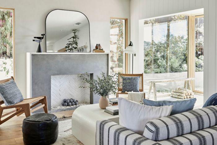 table basse blanche minimaliste canapé gris et blanc coussins decoratifs pouf cuir noir grands miroirs tapis oriental cheminée grise