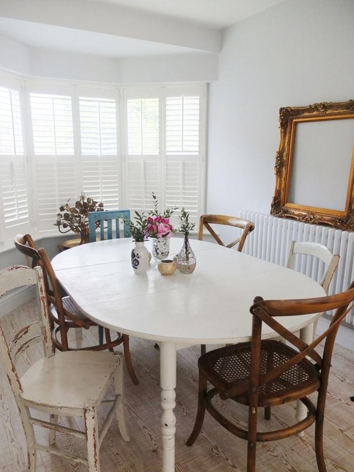 table ovale bois blanc chaise deco bois foncé cadre vide chaise bleu pastel vase verre fleurs séchées