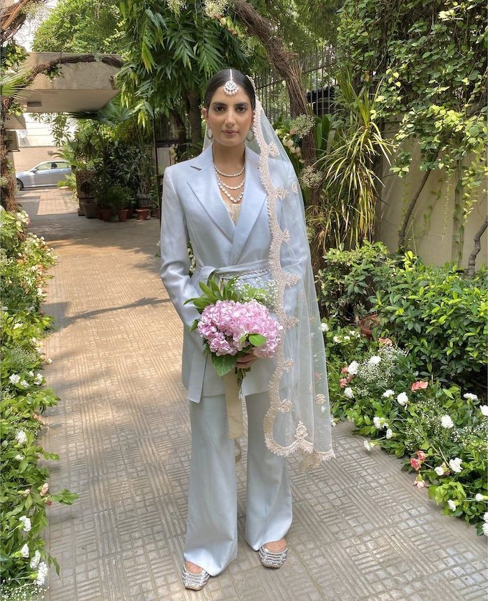 tailleur pantalon femme en bleu ciel pour une marriage une jeune femme dans un jardin tient un bouquet