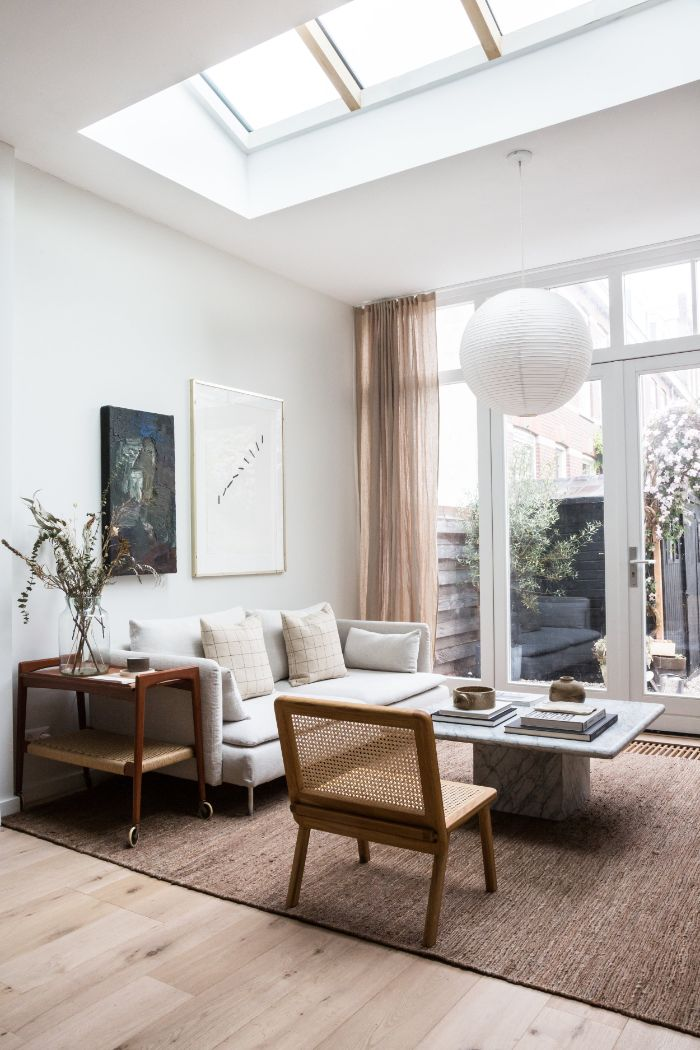 tapis fauve canapé gris clair table basse marbre chaise bois suspension blanche rideaux transparente verrière blanche et fenetre de toit