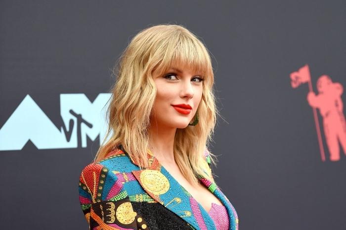 taylor swift idée coupe tendance 2021 célébrité coupe avec frange ondulations cheveux blonds
