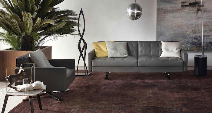 tendance chambre 2021 un tapis en couleur bordeaux canapé gris en cuir et une balle disco pendante du plafond