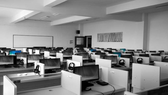 un bureau avec des tables et des oridnateurs image noir et blanc