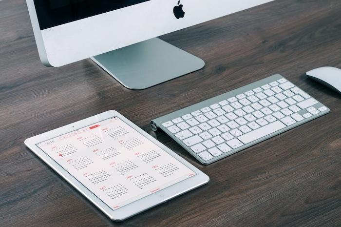 un calendar ouvert sur un ipad a cote d un ordinateur et clavier sur table en bois