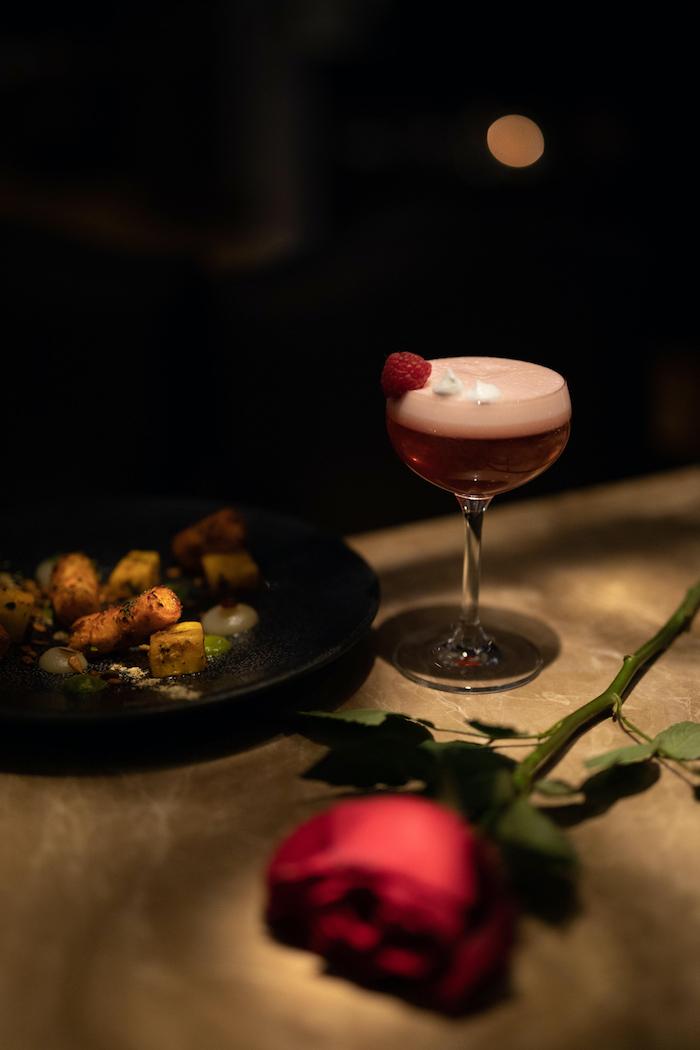 un cocktail de framboise a coté d un plat et d une rose idée de surprise pour saint valentin