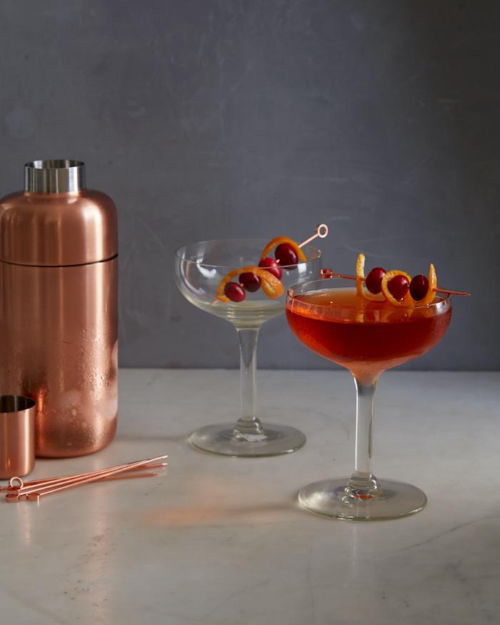 un cocktail rose sur un comptoir en marbre a coté d un shaker