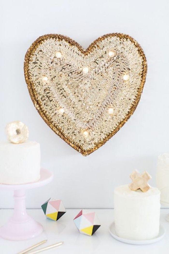 un coeur décoratif en pailletes sur un mur blanc décoration saint valentin