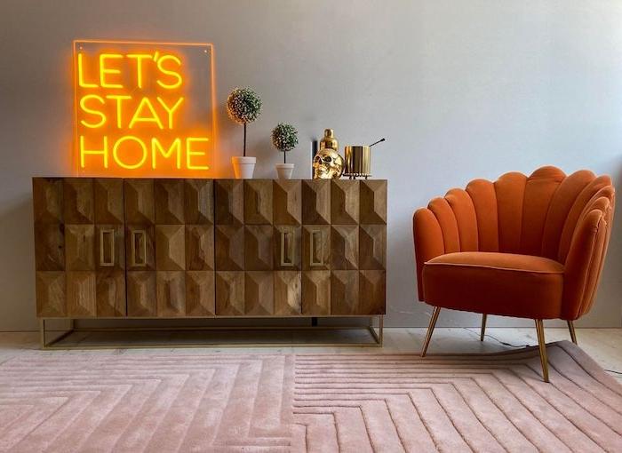 un comode en bolie a relief a coté d un fauteuil en ornage terreux et un message lumineux
