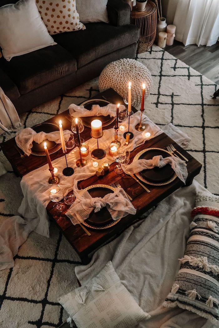 un diner servi sur un table basse en bois dans la salle de séjour avec un tapis blanc et des bougies allumés