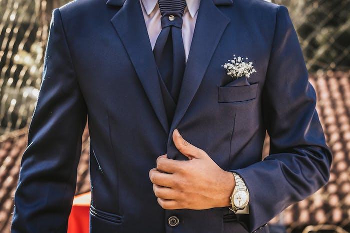 un homme vetu en costume bleu avec cravatte et montre autour de la poignée