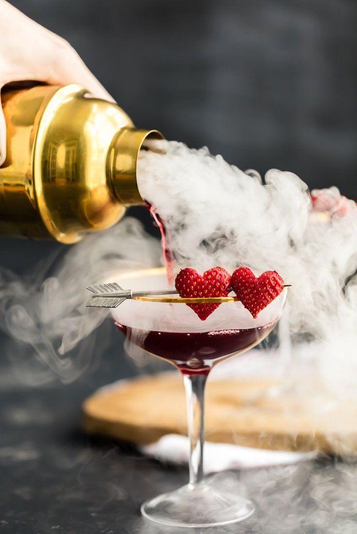 un main qui verse du cocktail dans un verre avec décore de fraises en forme de coeur