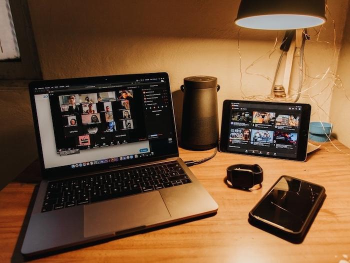 un ordinateur avec le logiciel zoom sur l ecran sut une table avec lampe